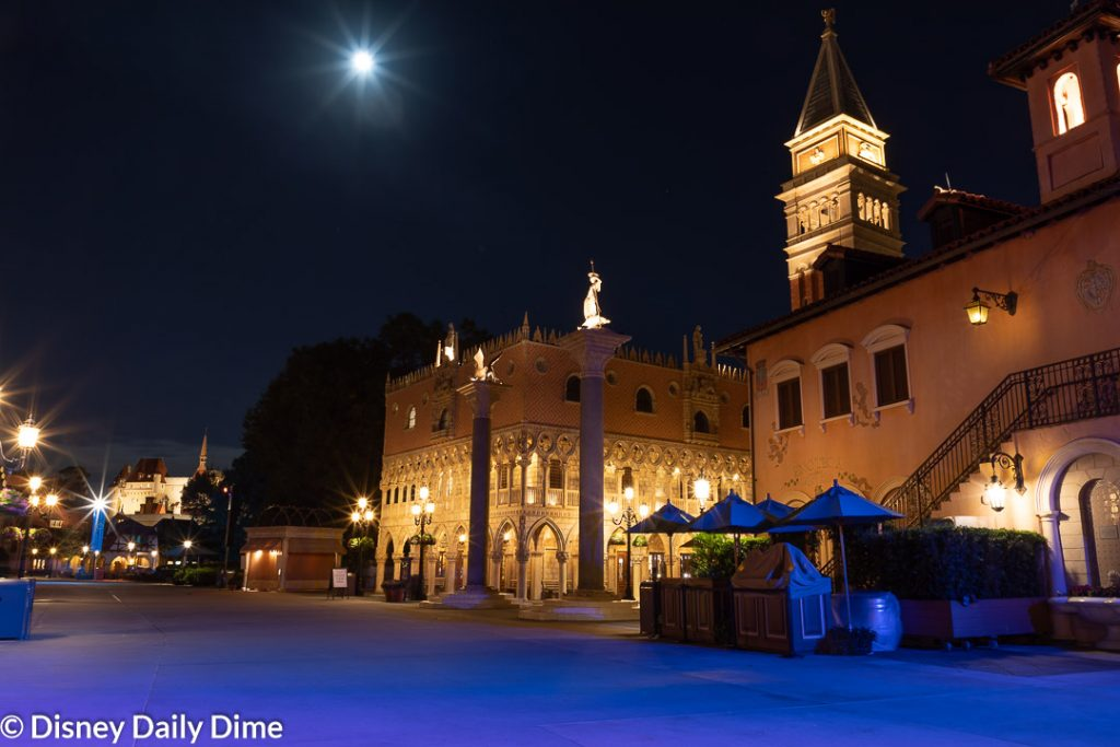 A night picture of the Italy pavilion in Epcot, with the moon rising in the back.